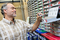 Happy mature man looking at staple pack in store