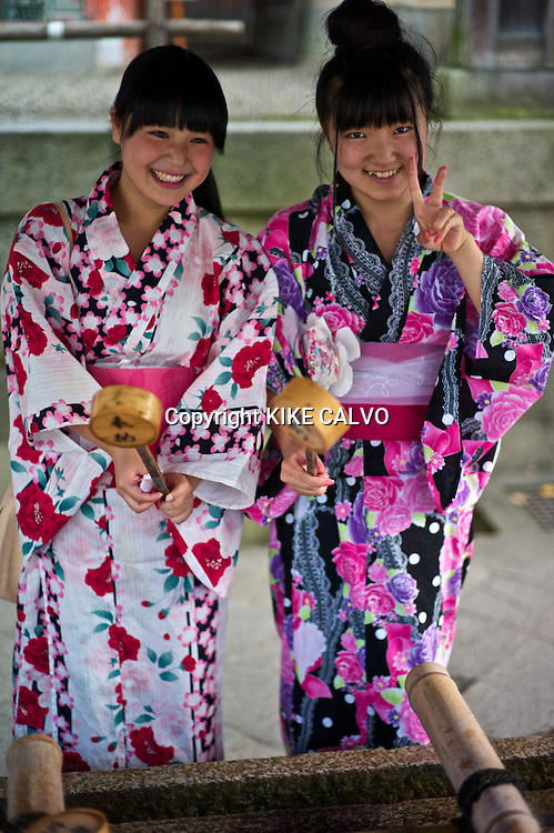 Two Asian teens wearing traditional kimonos at a Buddhist purification fountain in Kyoto.