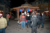 Fans watch the Olympic medal ceremonies on television screens at the Town Plaza during the 2010 Olympic Winter games in Whistler, BC Canada.