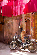 Motorbike parked up against colourful materials in the Dyers Souk, Marrakech Medina, Morocco
