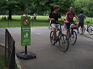 "Bikers riding their bicycles past the ""Walk Bikes on Paths"" sign at the Great Lawin in Central Park"
