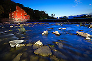 Water flows around rocks in the Raritan River as New Jersey's famous, historical Red Mill glows in the background.