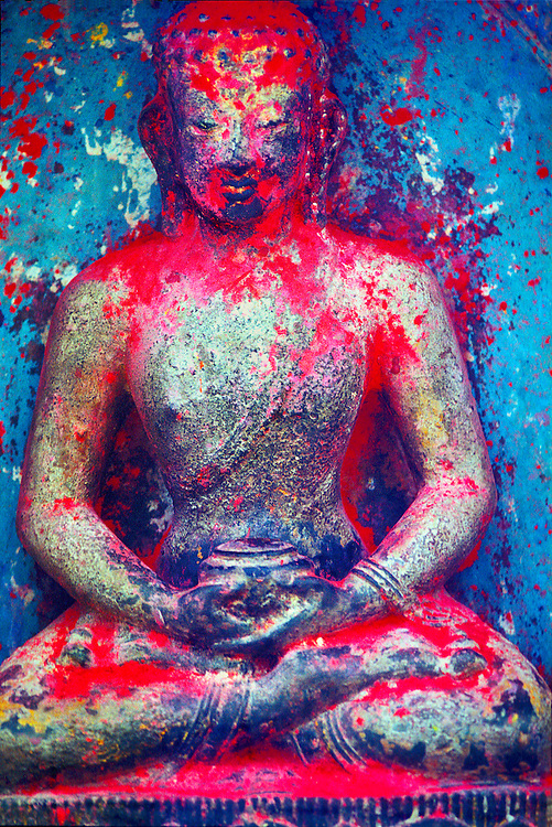 A Buddha statue, sprinkled with red vermillion powder, at the ancient Swyambhu religious complex (also known as The Monkey Temple) atop a hill in Nepal's Kathmandu Valley.