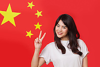 Portrait of mixed race young woman gesturing peace sign against Chinese flag