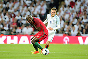 Portugal midfielder, Danilo (13) holding his face after a tackle from England forward, Jamie Vardy (11) during the Friendly International match between England and Portugal at Wembley Stadium, London, England on 2 June 2016. Photo by Matthew Redman.
