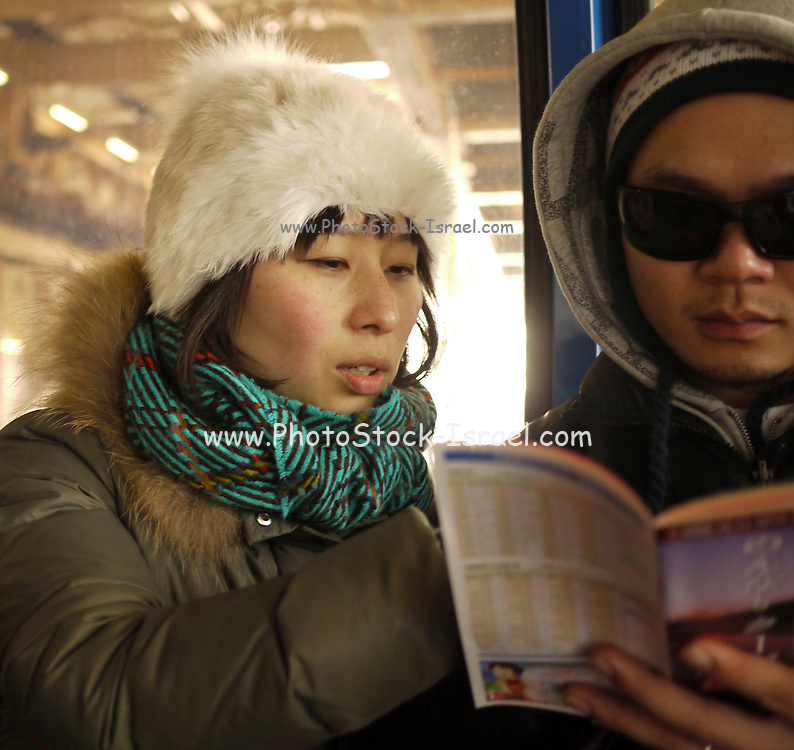 Japan Japanese tourists on the train read a guide book