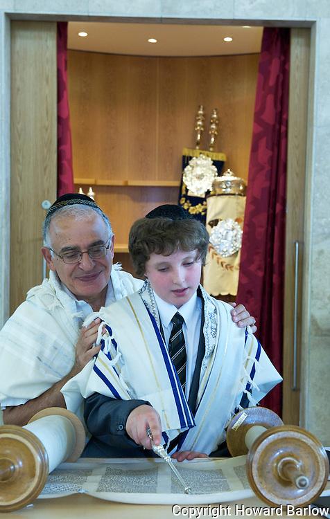 Rabbi teaches Barmitzvah boy his Torah portion from the Scroll