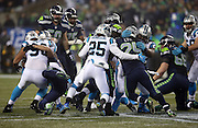 Seattle Seahawks running back Marshawn Lynch (24) gets gang tackled by Carolina Panthers cornerback Bene' Benwikere (25) and a teammate on a third down and one play in the first quarter during the NFL week 19 NFC Divisional Playoff football game against the Carolina Panthers on Saturday, Jan. 10, 2015 in Seattle. The Seahawks won the game 31-17. ©Paul Anthony Spinelli