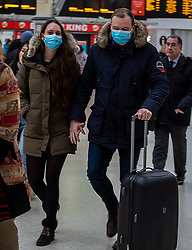 © Licensed to London News Pictures. 05/03/2020. London, UK. A couple holding hands head to work wearing masks at Victoria Station as the Government announces plans to combat the coronavirus disease crisis. Photo credit: Alex Lentati/LNP