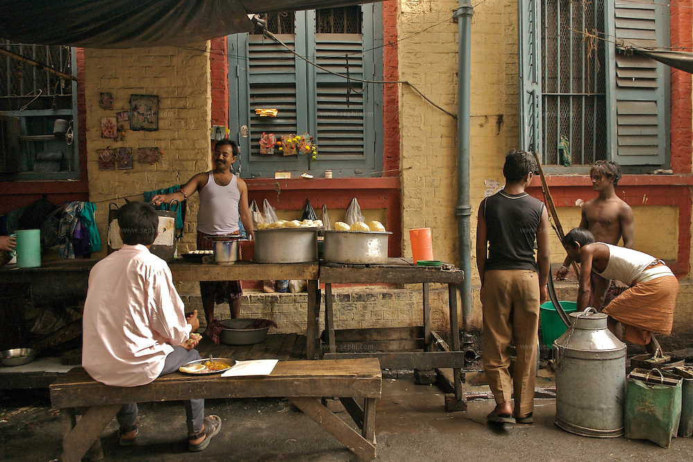 People fill up water containers on the street next to a food stall  selling Chhole Batora, Kolkata, January 2007