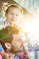 Portrait of man carrying his daughter on his shoulder in airport with lens flare