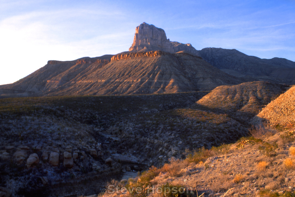 El Capitan at sunset, Guadalulpe Mountains National Park, Pine Spring Texas, August 1998.  Visible behind El Capitan is Guadalupe Peak, the highest point in Texas.  The Guadalupe Mountains are an exposed, fossilized reef.