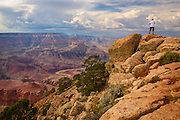 A hiker takes in the vista from atop some boulders on the South Rim of the Grand Canyon.
