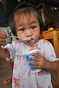 Portrait of a young girl in Laos eating yogurt