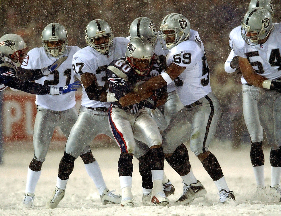 (1/19/02 Foxboro, MA) Patriots vs. Raiders at Foxboro Stadium. In heavy traffic, Pats (80) Troy Brown gets pulled down by a host of Raiders in the second quarter.  (011902patsMJS11.jpg- Staff Photo by Michael Seamans. Saved in Sunday/FTP)
