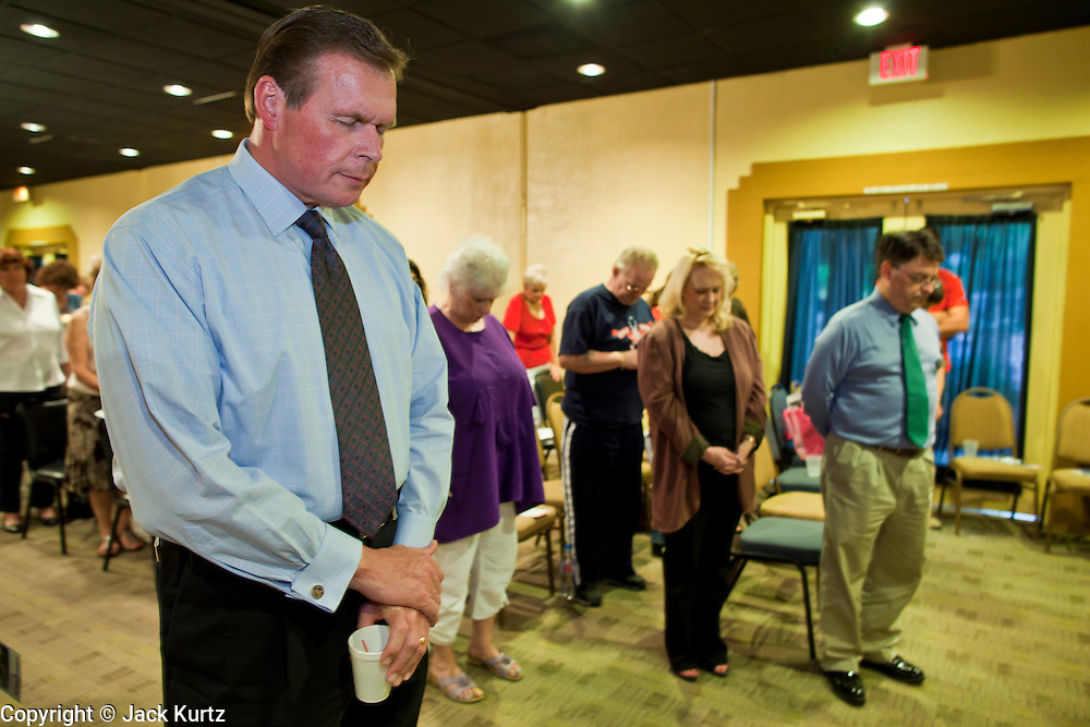 July 14 - PEORIA, AZ: JD HAYWORTH, a former Republican Congressman from Arizona, bows his head in prayer before speaking at a Tea Party meeting in Peoria, AZ. Hayworth spoke to a Tea Party gathering in a hotel meeting room in Peoria. Hayworth, an ultra conservative, is running to the right of long serving US Sen John McCain in the Arizona Republican US Senate primary. He has painted McCain as a moderate to liberal Senator in the mold John Kerry (D-MA).           Photo by Jack Kurtz