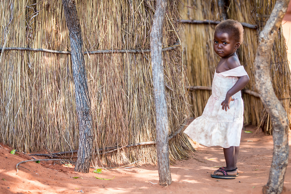 Young Zambian child stands next to hut as her dress blows in the wind, Mukuni Village, Zambia