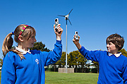 Milly Heane (10) and Joe Cave (10) measuring wind speeds with an anemometer to help determine best position for a second wind turbine on the school playing fields. St. Columb Minor School, Cornwall.