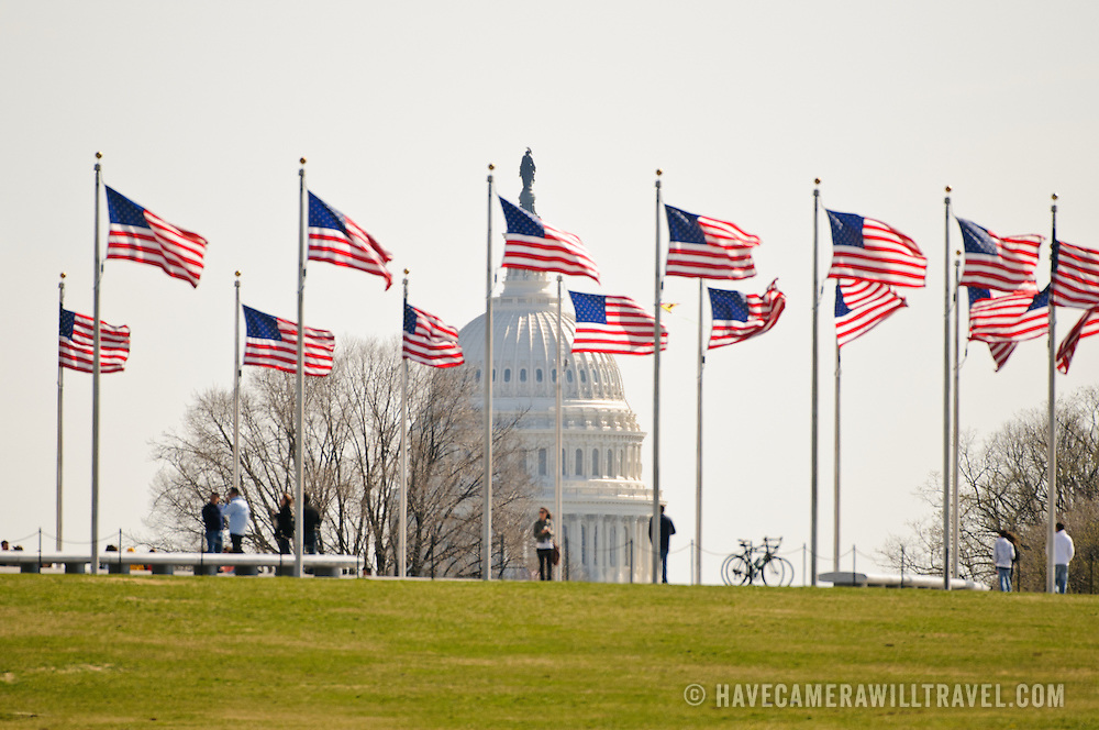 The US Capitol dome is seen in the distance past flags at the Washington Monument with tourists.