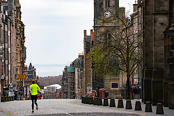 Edinburgh, Scotland, UK. 18 April 2020. Views of empty streets and members of the public outside on another Saturday during the coronavirus lockdown in Edinburgh. Woman running alone along empty Royal Mile. Iain Masterton/Alamy Live News