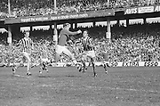 Cork player leaps in the air with the ball as Kilkenny swings his hurl out to block him during the All Ireland Senior Hurling Final, Cork v Kilkenny in Croke Park on the 3rd September 1972. Kilkenny 3-24, Cork 5-11.