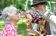 Maryann Lush (left) of Milford, Delaware is kissed by Django the monkey as his owner Jerry Brown holds him during the Tinicum Arts Festival which featured about 100 vendors and 180 artists and crafts people Saturday July 11, 2015 in Tinicum, Pennsylvania. (Photo by William Thomas Cain)