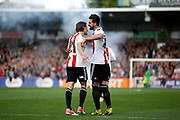 Brentford forward Lasse Vibe (21) and Brentford defender Yoann Barbet (29) celebrate his goal in front of a flare (score 1-0) during the EFL Sky Bet Championship match between Brentford and Queens Park Rangers at Griffin Park, London, England on 22 April 2017. Photo by Andy Walter.