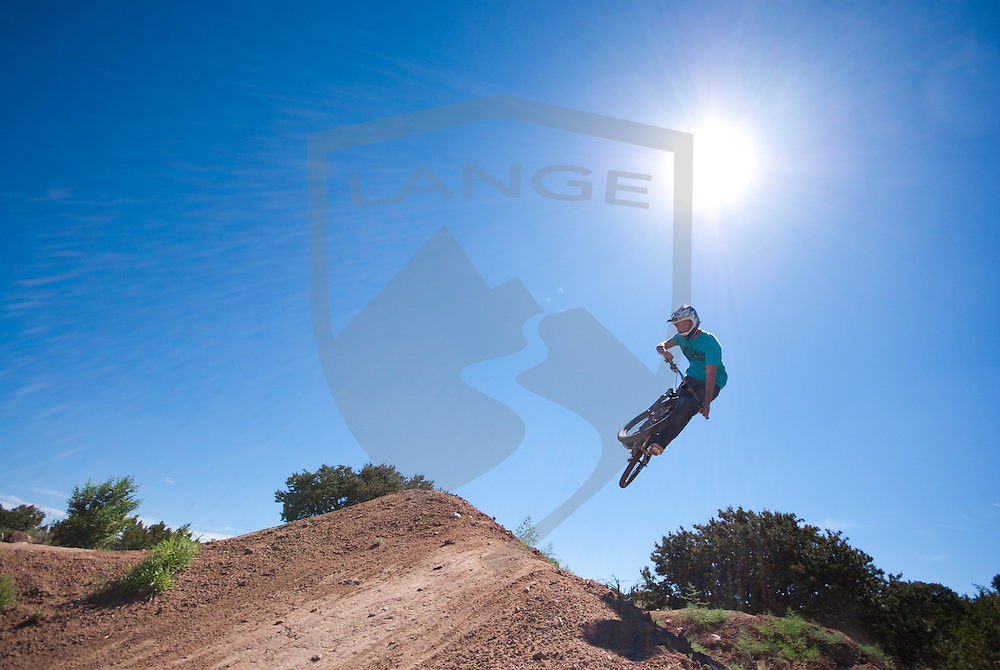 mountain bike rider matson hunter launches at the santa fe dirt jumps in santa fe, new mexico.