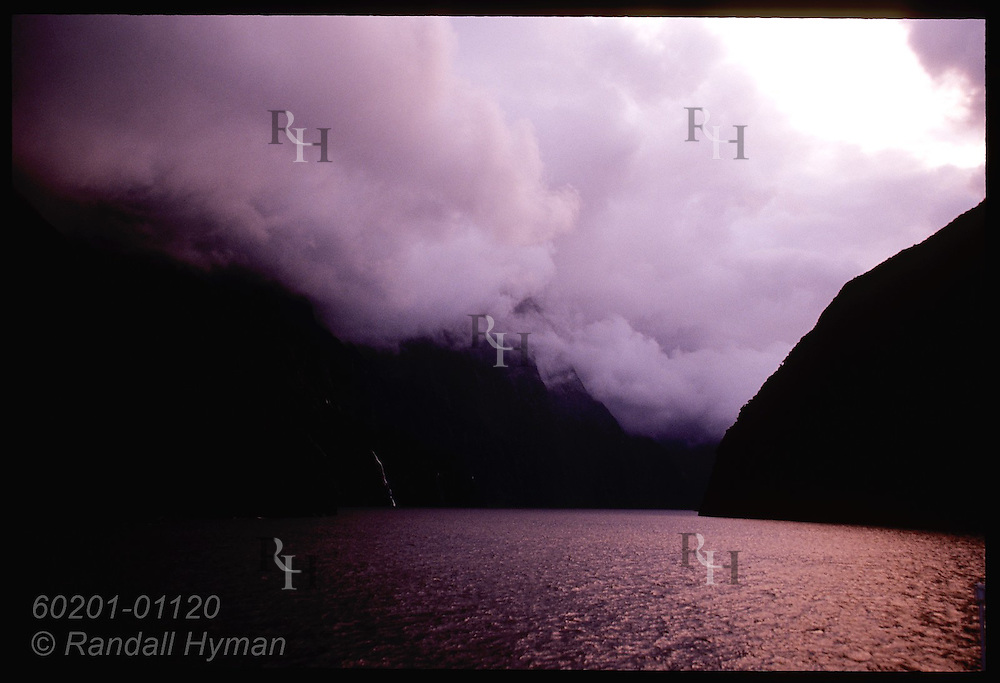 Storm clouds roil over Milford Sound in early morn; Fiordland National Park, New Zealand.