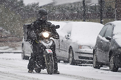 © Licensed to London News Pictures. 02/03/2018. London, UK. A man on a motorbike attempts to steady himself with his feet as further snowfall covers the landscape in Little Venice, Westminster, London. The 'Beast from the East' and Storm Emma have brought extreme cold, ice and heavy snow to the UK. Photo credit: Ben Cawthra/LNP