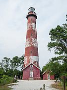 Assateague Light House was rebuilt 1867 in Virginia, USA. Assateague Light is 142 feet tall (43 m), located on the southern end of Assateague Island off the coast of the Virginia Eastern Shore. Reach it by road from Chincoteague Island via a bridge over Assateague Channel within the Chincoteague National Wildlife Refuge. Assateague Light is owned and operated by the U.S. Coast Guard and is still used as an active aid in navigation. The keeper's quarters are used as seasonal housing for refuge temporary employees, volunteers, and interns. Constructed in 1867 to replace a shorter lighthouse (45-feet-tall) built in 1833, the lighthouse is conical in shape and is painted in alternating bands of red and white.