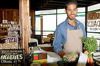 Portrait of handsome young store clerk holding vegetable in supermarket