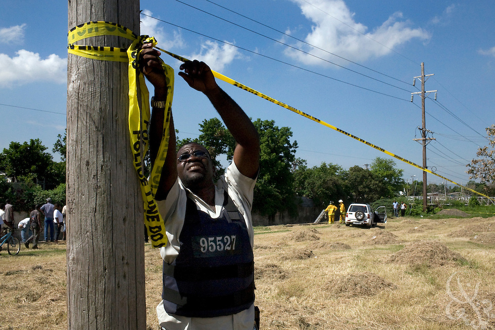 A Jamaican Constabulary Force (JCF) police officer tapes off the crime scene where the body of a murder victim was found dumped in a gully in the Meadowbrook Estate neighborhood of Kingston June 13, 2008.