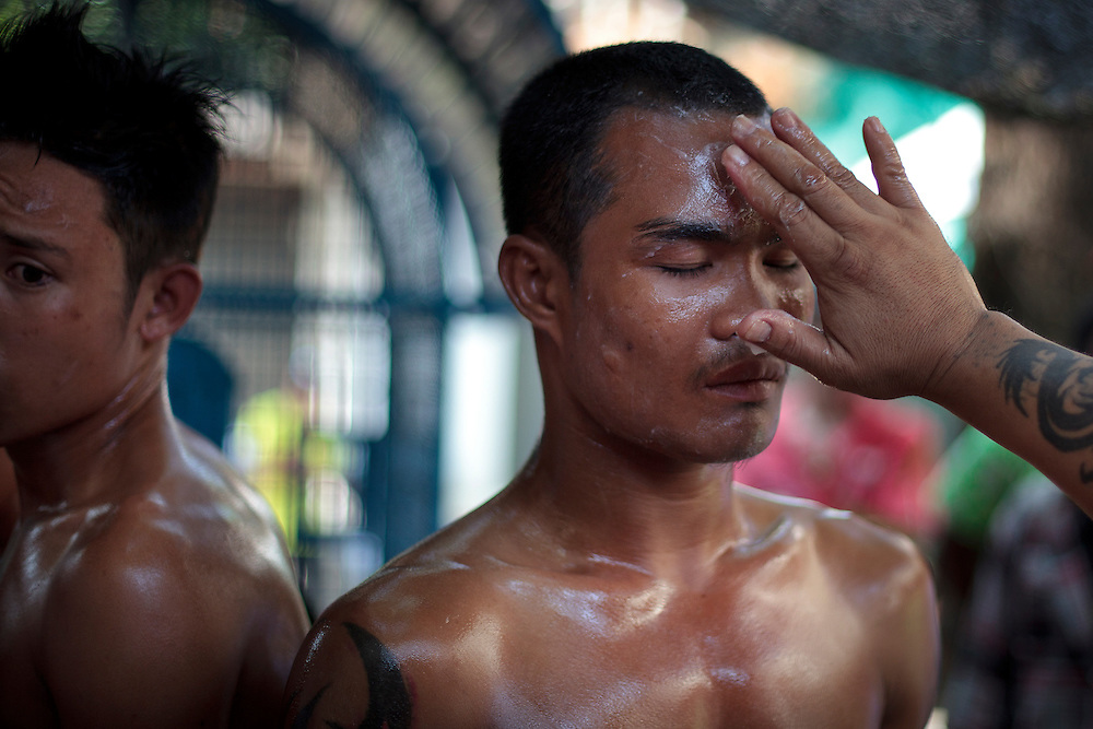 Thailand's Muay thai fighter, right, is seen during the preparation before the traditional Songkran fight beside to Myanmar-Thailand friendship bridge, Mae sot, Thailand on Friday, April. 13, 2012. Songkran festival is the Thai traditional New Year from April 13 to 15.