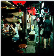 Young couple share beer as two young Tokyoite women look for a seafood or noodle restaurant to have dinner, Shinjuku, Tokyo, Japan.
