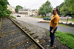 Mayor Peter Ursucheler stands at a small abounded stretch of railroad that remains along Bridge Street, near the former train station, in Phoenixville, PA, on august 21, 2018. (Bastiaan Slabbers for WHYY)