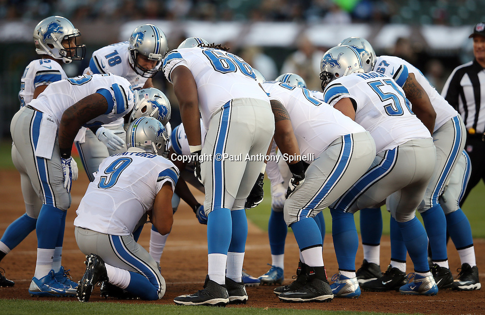 Detroit Lions quarterback Matthew Stafford (9) huddles with the offense and calls a play during the 2014 NFL preseason football game against the Oakland Raiders on Friday, Aug. 15, 2014 in Oakland, Calif. The Raiders won the game 27-26. ©Paul Anthony Spinelli