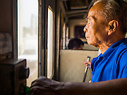 19 MARCH 2015 - AYUTTHAYA, AYUTTHAYA, THAILAND:  A passenger on a third class train near Ayutthaya. The train line from Bangkok to Ayutthaya was the first rail built in Thailand and was opened in 1892. The State Railways of Thailand (SRT), established in 1890, operates 4,043 kilometers of meter gauge track that reaches most parts of Thailand. Much of the track and many of the trains are poorly maintained and trains frequently run late. Accidents and mishaps are also commonplace. Successive governments, including the current military government, have promised to upgrade rail services. The military government has signed contracts with China to upgrade rail lines and bring high speed rail to Thailand. Japan has also expressed an interest in working on the Thai train system. Third class train travel is very inexpensive. Many lines are free for Thai citizens and even lines that aren't free are only a few Baht. Many third class tickets are under the equivalent of a dollar. Third class cars are not air-conditioned.   PHOTO BY JACK KURTZ