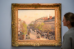 "© Licensed to London News Pictures. 14/06/2019. LONDON, UK.  A staff member views ""Le Boulevard Monmatre, Fin de Journee"", 1897, by Camille Pisarro (Est. £3.5-5.0m). Preview of Impressionist and Modern art sales, which will take place at Sotheby's New Bond Street on 18 and 19 June 2019.  Photo credit: Stephen Chung/LNP"