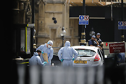 © Licensed to London News Pictures. 14/08/2018. London, UK. Forensic officers investigate the car crushed into security barriers outside Houses of Parliament in London on August 14, 2018. Police say car crash is being treated as terror attack. Photo credit: Tolga Akmen/LNP