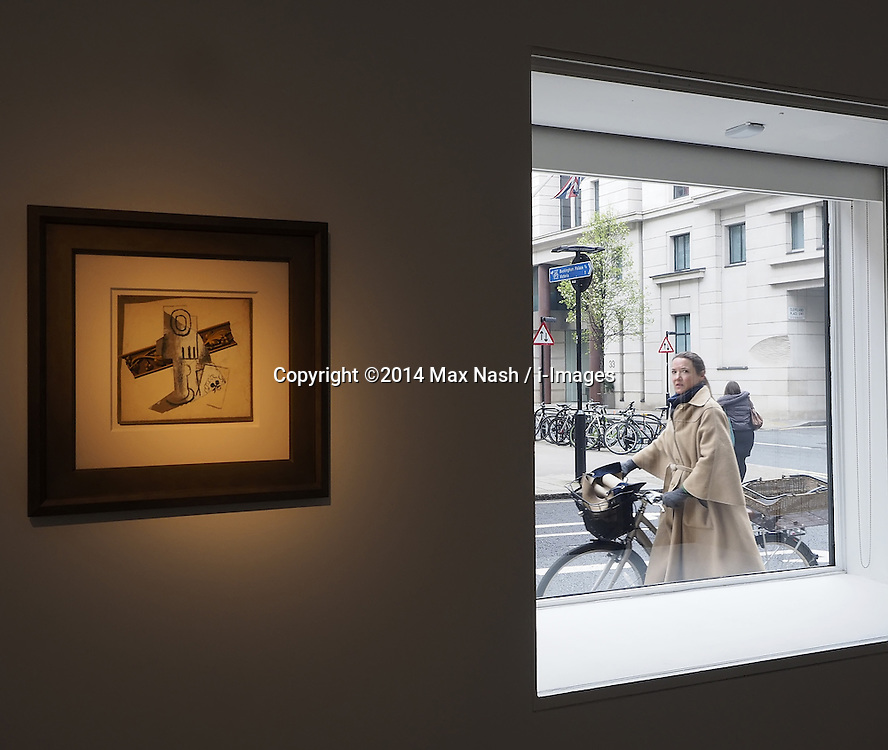 An unidentified cyclist walks past the art exhibition with Pablo Picasso's 'Verre et Carte a Jouer', (estimated at $600,000-*00,000)on the wall left, at Christies Impressionist and Modern Art. display of highlights for the uncoming New York auction on May 6, 2014. Photo taken in London, United Kingdom. Friday, 28th March 2014. Picture by Max Nash / i-Images