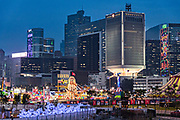 Hong Kong Island skyline with the annual winter carnival at the AIA Vitality Park in the Central District of Hong Kong.