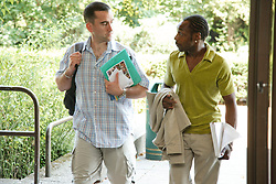 Man with hearing impairment with fellow student going into university library.