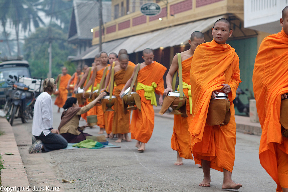 "15 MARCH 2009 -- LUANG PRABANG, LAOS: Buddhist Monks in Luang Prabang, Laos, go about their ""Tak Bat,"" Lao for ""monks morning rounds."" The monks collect alms in the form of food from people who line their route. For the monks, it is the only food they get that day, for the people it's a chance to ""make merit."" Luang Prabang is a UNESCO World Heritage Site and the spiritual capital of Laos. There are dozens of ""wats"" or temples and thousands of monks in the city. It is still the center of Buddhist education in Laos. PHOTO BY JACK KURTZ"