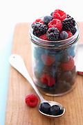 Jar full of raspberries blackberries and blueberries on cutting board