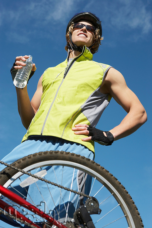 Male cyclist holding water bottle, outdoors