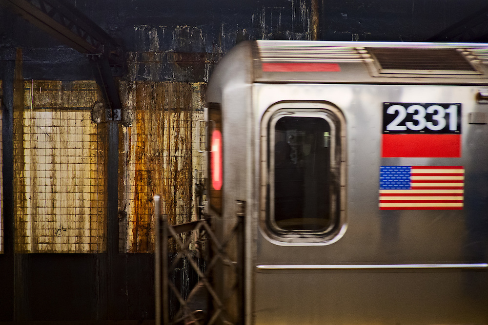 Subway train pulling into Canal Street station, past corroded wall.  New York, NY, US