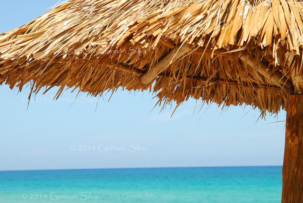 At the beach, underneath a &quot;palapa&quot;.  Calm, aqua green / blue, Caribbean Sea, light blue sky.  Sunny day.  At the beach - Santa Maria beach, Cuba<br /> En la playa, bajo una palapa.  Verde azulado, calmo Mar Caribe.  Dia soleado.  En la playa.  <br /> Playa de Sant