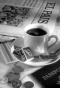 demi tasses coffee on cafe table with newspaper,passport,foreign money,tip chart.