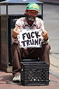 A beggar sits on Bourbon Street in the French Quarter protesting Donald Trump.